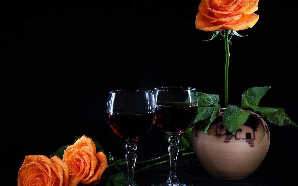 Обои для рабочего стола Два бокала с красным вином, керамический горшок с цветущей оранжевой розой в капельках воды и два лежащих цветка розы