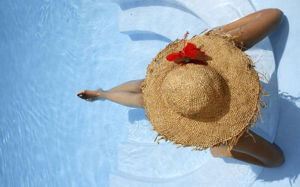 Обои для рабочего стола Девушка в соломенной шляпе сидит в бассейне