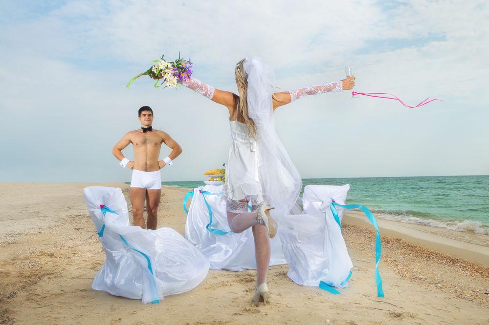 Обои для рабочего стола Девушка в свадебном платье и с букетом цветов в руках бежит по берегу моря навстречу мужчине, который стоит в одних трусах и с бабочкой на шее