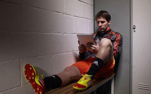 Обои Известный футболист Лионель Месси /  Lionel Messi сидит с планшетом в руках на лавке в раздевалке