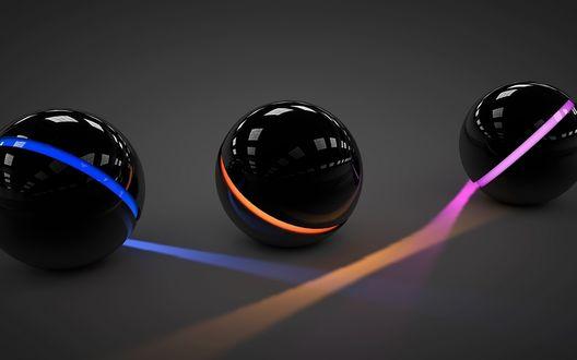 Обои Три чёрных шарика с неоновыми светящимися синей, оранжевой и розовой полосками