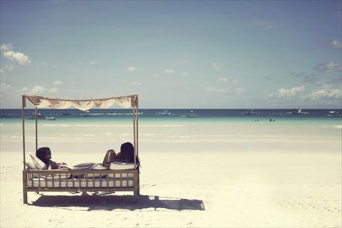 Обои Две девушки сидят на мягкой скамейке с навесом и любуются видом на море