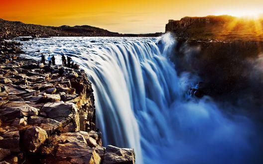 Обои У водопада, освещенного утренними лучами восходящего солнца, стоят туристы
