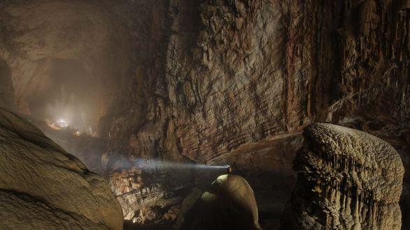 Обои Спелеолог, стоящий на каменном валуне пещеры, с помощью фонарика с мощным световым лучом начинает осмотр стен