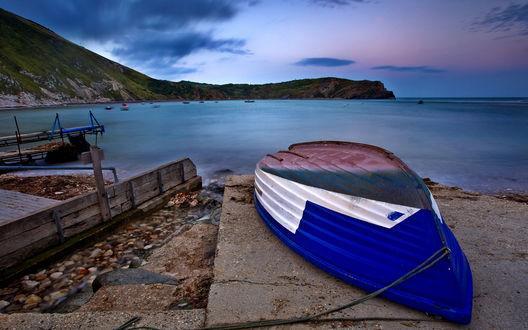 Обои Прогулочная лодка, покрашенная в белый и синей цвета, сушится на бетонной плите на берегу озера