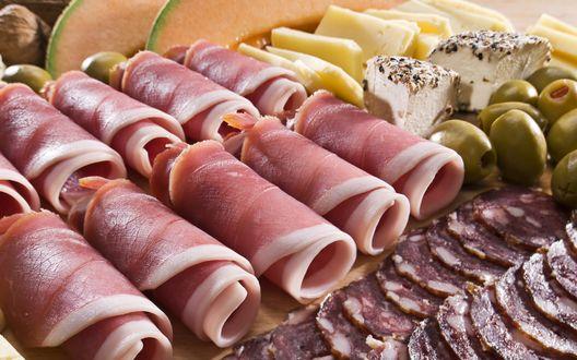 Обои Рулеты из бекона, нарезка колбасы, сыра, рядом буженина и оливки