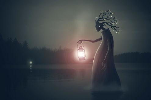 Обои Старое мрачное дерево с огоньками на концах веток и в 'глазах' стоит ночью, посреди темного озера с фонарем в 'руках'  и подает знак на противоположный берег, в лес, откуда тоже виден свет