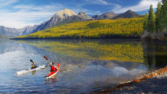 Обои Мужчина и женщина подплывают на байдарках к берегу горного озера, покрытого зеленью