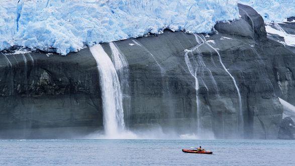 Обои Мужчина проплывает на лодке мимо огромной скалы с падающими водопадами, образовавшимися от таяния льдины наверху скалы