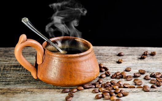 Обои Чашка с металлической ложечкой и свежезаваренным кофе с дымком, стоящая на деревянном столе среди кофейных зерен