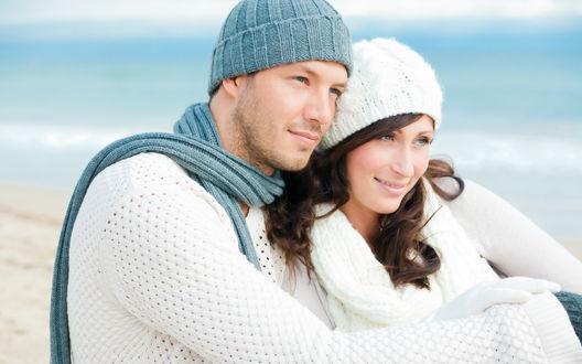 Обои Парень и девушка, обнявшись, сидят на берегу моря и смотрят в одну сторону