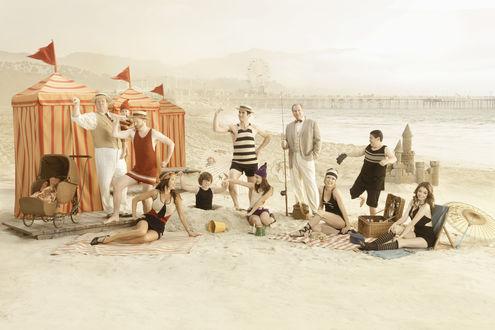 Обои Главные герои сериала Американская семейка / Modern Family на пляже в цирковых костюмах на фоне пирса