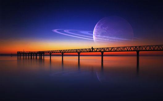 Обои Рыбак с удочкой стоит на мосту океанского побережья на фоне заката с изображением планеты Сатурн