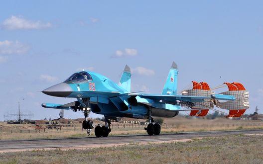 Обои Многоцелевой истребитель Российских ВВС Су-34 производит посадку на бетонную взлетно-посадочную полосу с выпущенными тормозными парашютами