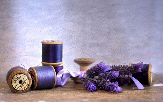 Обои Фиолетовые цветы лаванды лежат рядом с деревянными катушками с фиолетовыми нитками
