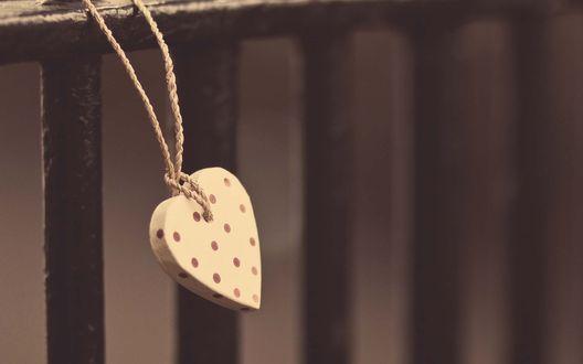 Обои Картонное сердечко на веревке привязано к черному железному ограждению