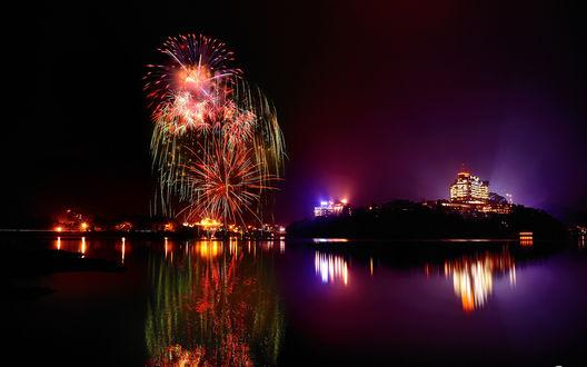 Обои Красочный фейерверк в ночном небе над городом, стоящим на морском побережье