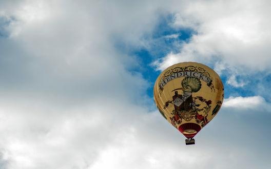 Обои Спортивный воздушный шар, парящий в голубом небе с белыми облаками и рекламным рисунком птицы, держащей бутылку с надписью 'HENDRISKS / Джин Хендрикс'