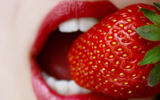 Обои Девушка с ярко-красными, накрашенными губами кусает спелую клубнику