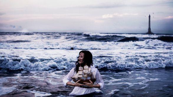 Обои Девушка-брюнетка в белом платье, стоящая в морской прибрежной воде, держащая в руках модель парусного судна на фоне пасмурного неба и маяка