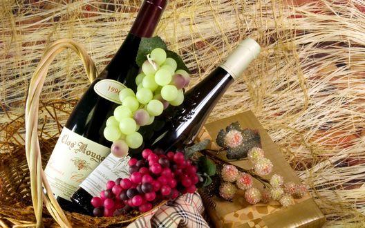 Обои Две бутылки вина и виноград лежат в плетеной корзине, которая стоит рядом с веточкой цветов и подарка