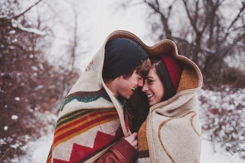 Обои Парень с девушкой укутались в одеяло на фоне снежных деревьев