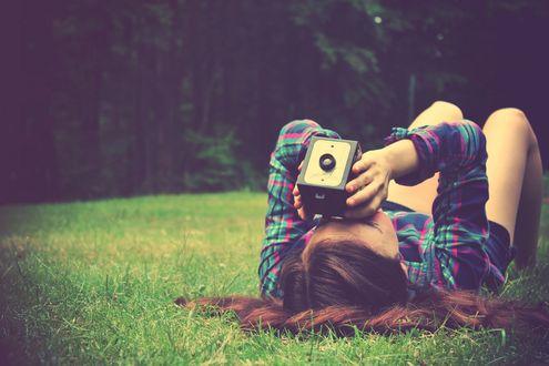 Обои Девушка лежит на траве и смотрит в камеру
