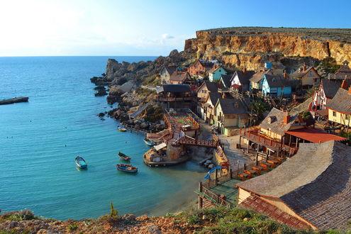 Обои Деревня сделанная из декорации к фильму Деревня Попая / Popeye Village на берегу океана, у побережья, лодки, Мальта / Malta