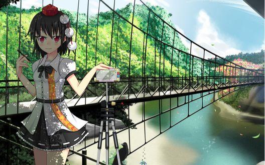 Обои Aya Shameimaru / Ая Шамеймару из серии игр Тохо / Touhou Project стоит у моста рядом со штативом, держа в одной руке ручку, а другую положив на камеру