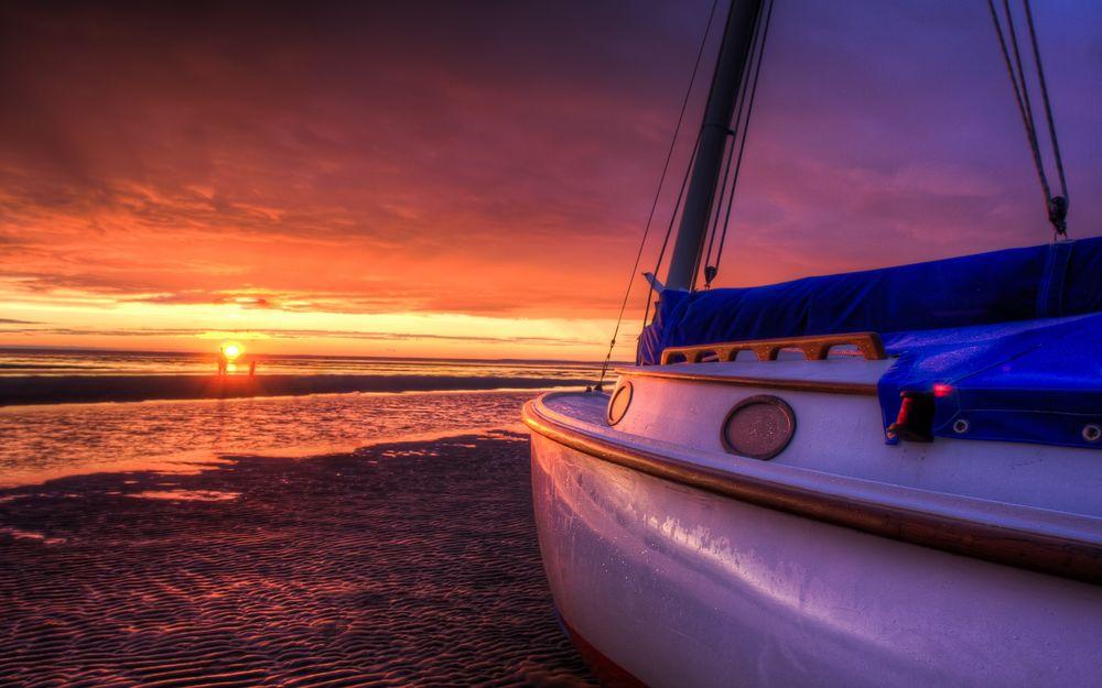 Обои для рабочего стола Яхта, стоящая на песчаном морском побережье, на фоне заходящего солнца