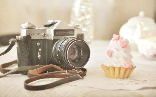 Обои Фотоаппарат Zenit-E лежит на столе, рядом с пирожным, украшенным розовыми сердечками