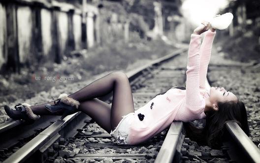Обои Девушка азиатка в нежно-розовом свитере, черных капроновых колготках и сапожках с мехом, лежит на рельсовых путях, подняв руки с чем-то белым, вязаным и пушистым вверх (Huu Trong Nguyen)