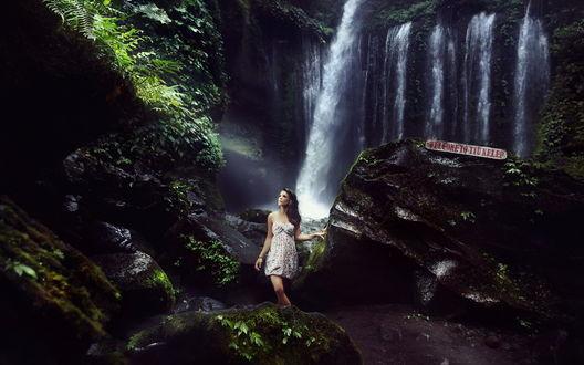 Обои Девушка шатенка в платье стоит на фоне знаменитого водопада Tiu Kelep, расположенного на острове Ломбок, Индонезия / Lombok, Indonesia, на камне надпись WELCOME TO TIU KELEP / Добро пожаловать на водопад Tiu Kelep