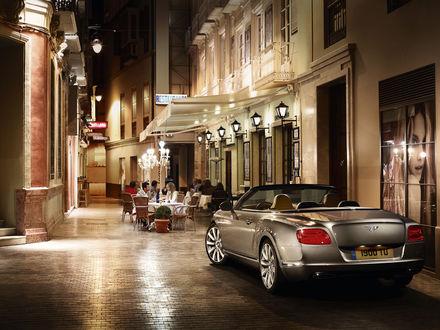 Обои Автомобиль Bentley Continental GT стоит у бутика на узкой вечерней улице, за столиками кафе увлеченно беседуют люди