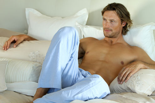 Обои Актер и модель Габриэль Обри / Gabriel Aubry с голым торсом лежит на кровати