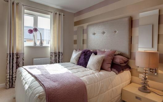 Обои Красивый интерьер спальни: рядом с кроватью стоит тумбочка с ночником, на стене висят зеркала, на подоконнике стоят две вазы с сиреневыми цветами