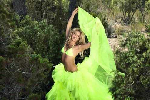 Обои Певица Шакира / Shakira в ярко-салатовой юбке и купальнике стоит среди кустов и деревьев