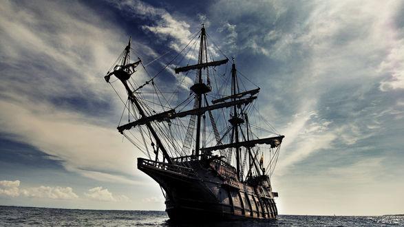 Обои Двухмачтовый корабль со спущенными парусами дрейфует в море