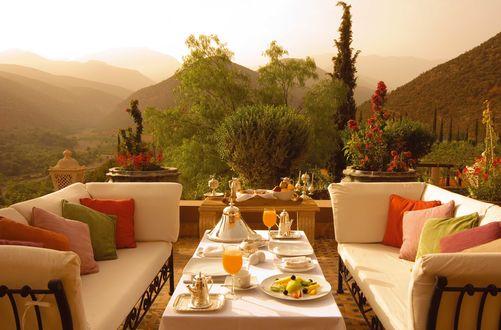 Обои Терраса с видом на затуманенные горы, на стол поданы фрукты и сок, а на диваны разложено множество подушек для комфорта гостей в отеле Kasbah Tamadot 5 в Марокко / Morocco