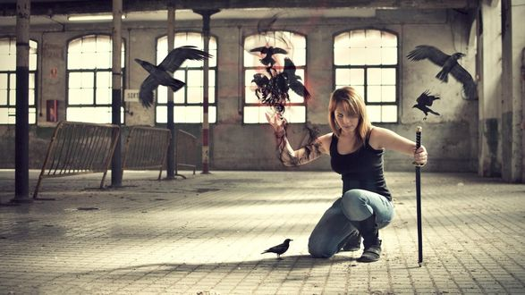 Обои Девушка с мечом сидит на колене пускает из руки ворон
