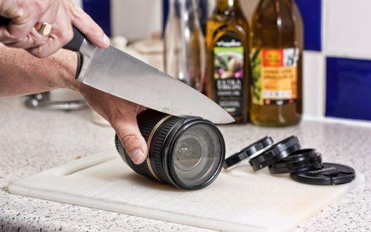 Обои Мужчина нарезает линзу фотокамеры большим ножом на кухонном столе