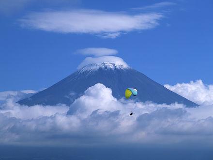Обои Парашютист на фоне горы, возвышающейся над облаками