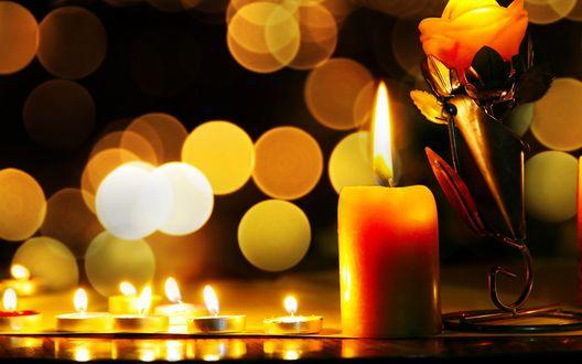 Обои Свеча стоит на черном фоне с огнями