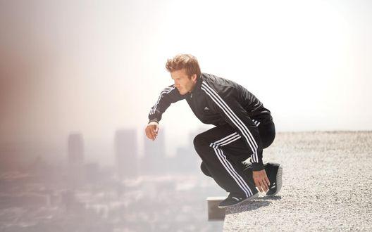 Обои Дэвид Бекхэм / David Beckham в черных кроссовках и спортивном костюме в белую полоску от Адидас / Adidas собирается прыгнуть с крыши многоэтажного дома