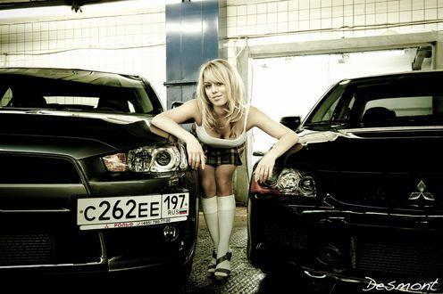 Обои Блондинка стоит между двумя автомобилями в гараже