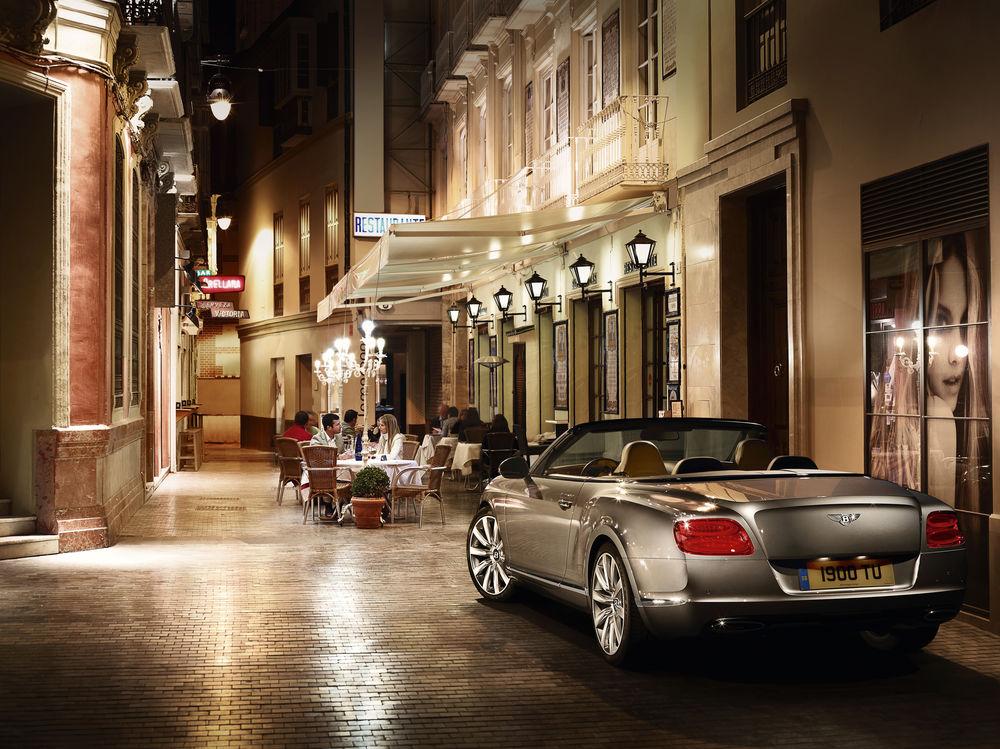 Обои для рабочего стола Автомобиль Bentley Continental GT стоит у бутика на узкой вечерней улице, за столиками кафе увлеченно беседуют люди