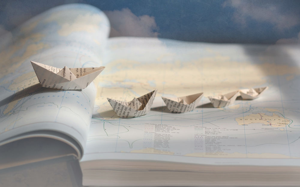 Обои для рабочего стола Бумажные кораблики расставлены на карте в атласе