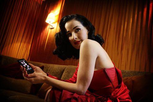 Обои Dita Von Teese / Дита фон Тиз в красном платье сидит на диване и держит в руках телефон