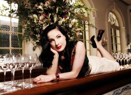 Обои Dita Von Teese / Дита фон Тиз лежит на барной стойке, смотря куда-то