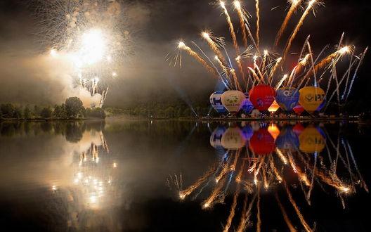 Обои Разноцветные воздушные шары, находящиеся на берегу озера, готовятся к старту в ночное небо на фоне огненных вспышек фейерверка